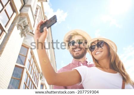 Happy girl making selfie with her boyfriend near by - stock photo