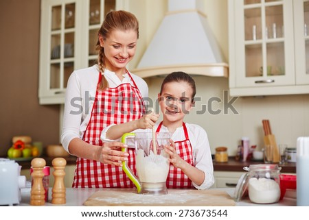 Happy girl mixing dough with her mother near by