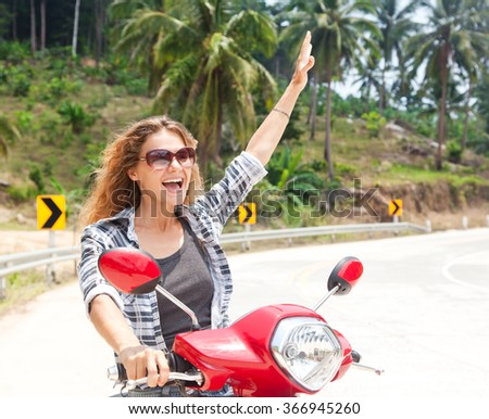 happy girl on a motorbike, the road on a tropical island - stock photo