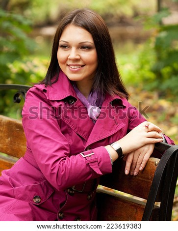happy girl on bench in autumn park