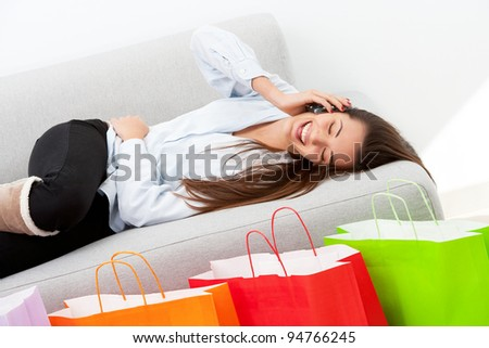 Happy girl on couch talking on mobile phone in front of shopping bags. - stock photo