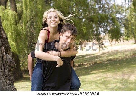 Happy girl on piggyback of boy friend in park