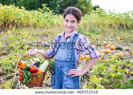 Happy girl on rural landscape with basket of vegetables