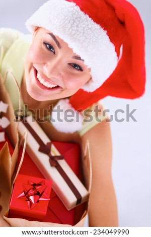 Happy girl on santa hat with gift box on red background - stock photo