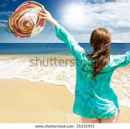 Happy girl on the beach against blue sea - stock photo