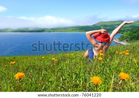 happy girl on the flower meadow against the sea landscape - stock photo