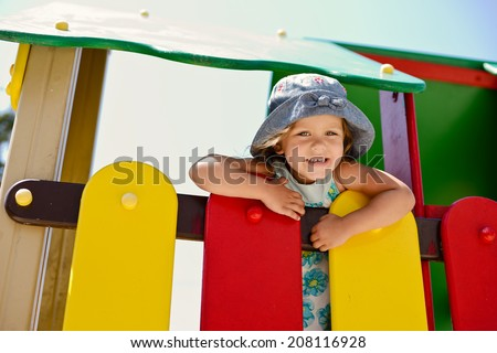 happy girl on the playground in summer
