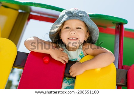 happy girl on the playground in summer - stock photo