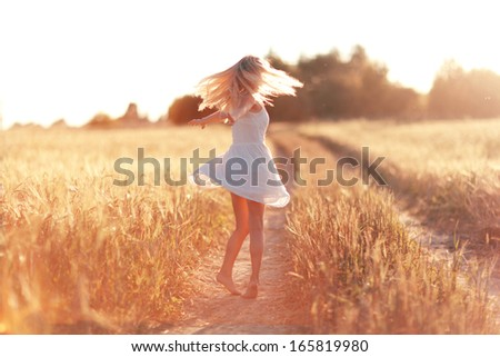 happy girl on the road in a wheat field at sunset - stock photo