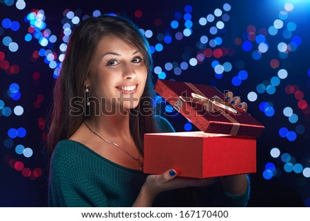 Happy girl opening Christmas box wich is glowing inside
