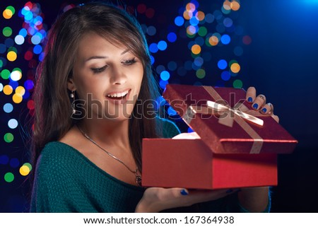 Happy girl opening Christmas box wich is glowing inside - stock photo