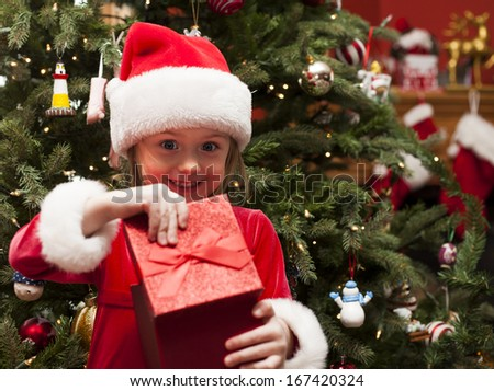 Happy girl opening Christmas present at home  - stock photo
