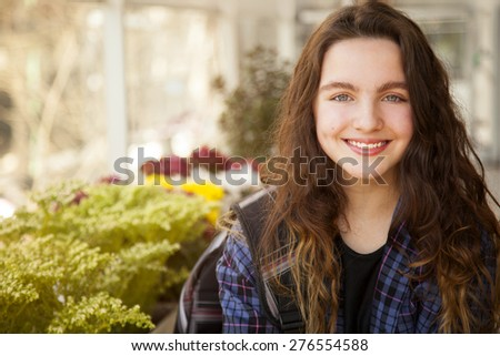 Happy girl outdoors, smiling and looking at camera - stock photo