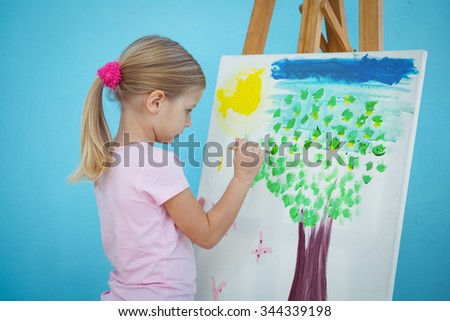 Happy girl painting her picture on an easel - stock photo