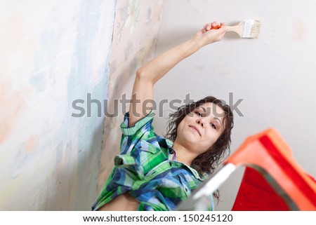 Happy girl paints ceiling with brush at home  - stock photo