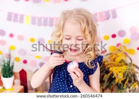 happy girl paints easter eggs  - stock photo