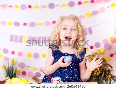 happy girl paints easter eggs, smiling - stock photo