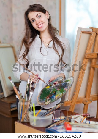 Happy girl paints on canvas with oil colors in workshop - stock photo