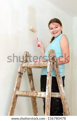 Happy girl paints wall with roller