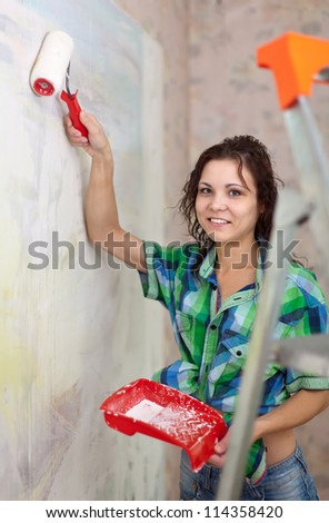 Happy girl paints wall with roller at home - stock photo