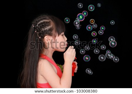 Happy girl play with soap bubbles isolated black background - stock photo