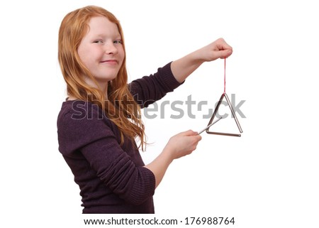 Happy girl playing a triangle instrument on white background  - stock photo