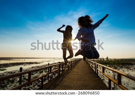 happy girl playing at the sunrise time,friendship concept - stock photo