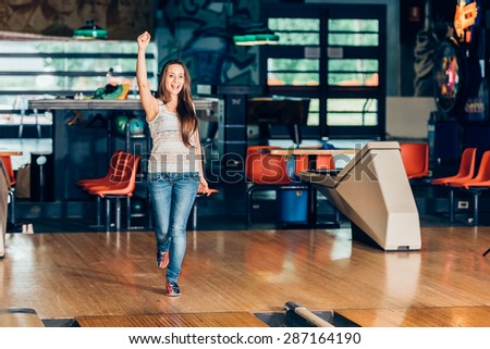 happy girl playing bowling - stock photo