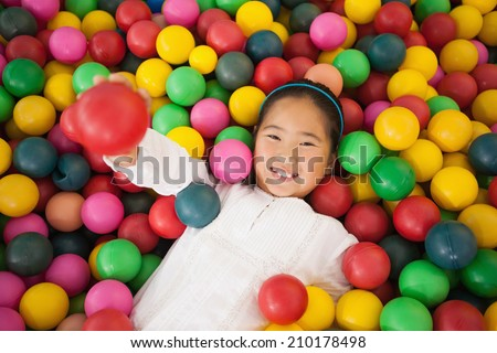 Happy girl playing in ball pool at a party - stock photo