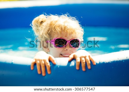 Happy girl playing in blue swimming pool. Summer holidays.