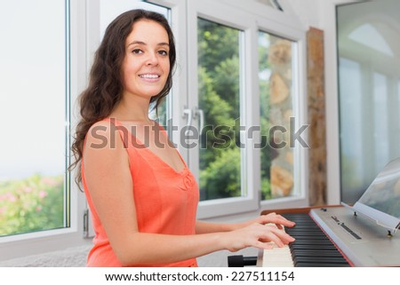 Happy girl playing piano at home and smiling - stock photo