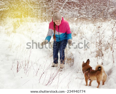 Happy girl playing with dog in winter forest