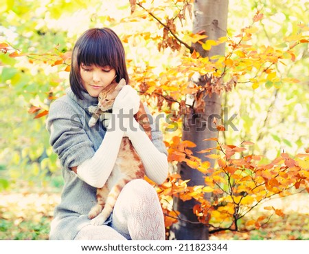 Happy girl portrait playing with ginger cat, autumn outdoor.  - stock photo