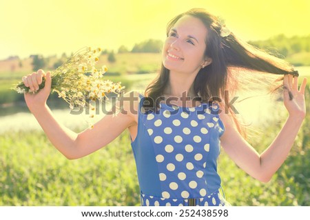 Happy girl posing and holding flowers. On nature - stock photo