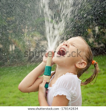 Happy girl pouring water from a hose - stock photo