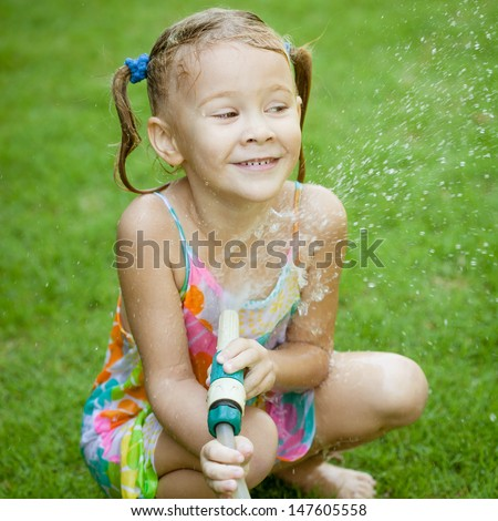 Happy girl pours water from a hose - stock photo