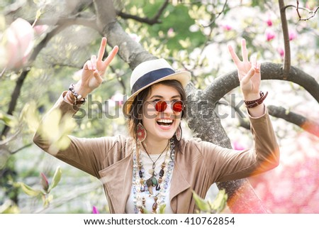 Happy girl rejoices in the spring garden. A girl dressed in boho style. Street fashion. Girl on nature. Accessories, sunglasses, necklaces, bracelets, watches, hat. - stock photo