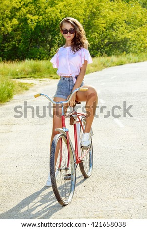 Happy girl riding a bicycle in the park on a summer day. Summer holidays.