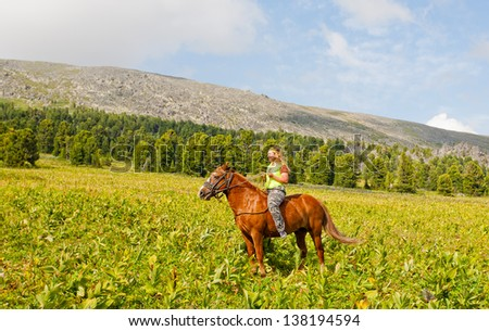 Happy girl riding a horse bareback at mountains - stock photo