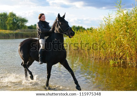 Happy girl riding horse in shallow river water - stock photo
