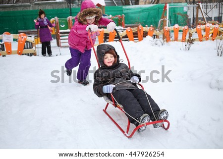 Happy girl rolling a little boy on a sled in front of the girl on skis in the winter playground - stock photo
