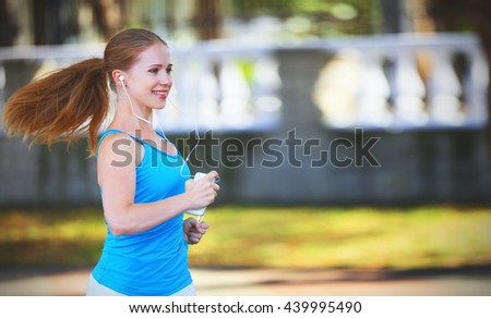 happy girl runner in for sports and fitness in the summer in the park - stock photo
