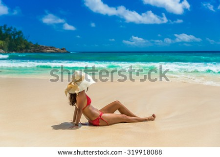 Happy girl running at beautiful beach on tropical island in Seychelles