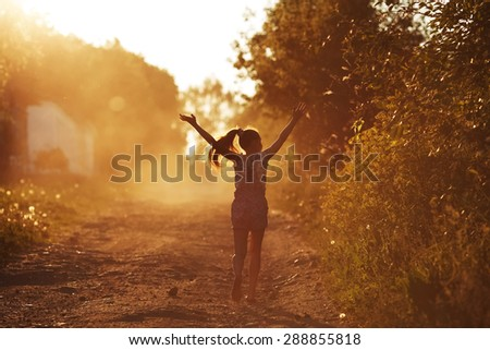 Happy girl running on a dusty road in the summer - stock photo