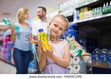 Happy girl selecting non-alcoholic beverage in plastic bottle in food store - stock photo