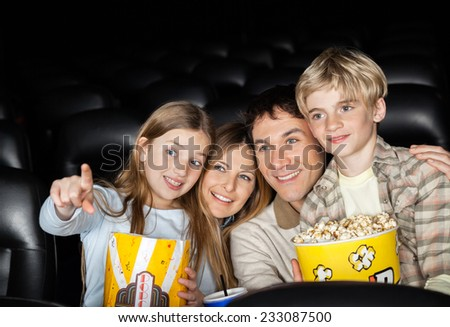 Happy girl showing something to family while watching movie in cinema theater - stock photo