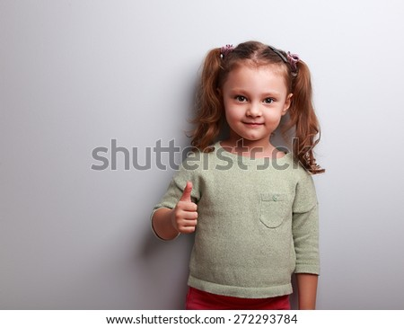 Happy girl showing thumb up sign on blue background with empty copy space - stock photo