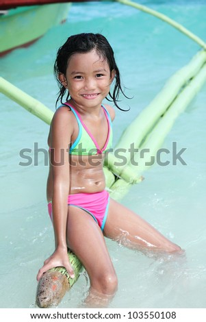 Happy girl sitting at the side of a wooden boat. - stock photo