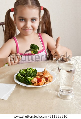 Happy girl sitting at the table and shows the thumb - stock photo