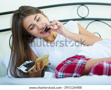 Happy girl sitting in bed and eating dark chocolate indoors - stock photo